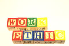 The term work ethic. Displayed visually using colorful wooden toy blocks Stock Photos
