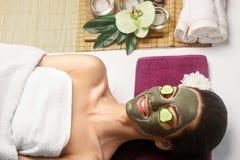 Termas Clay Mask Mulher com máscara facial da argila e pepinos no olho fotos de stock