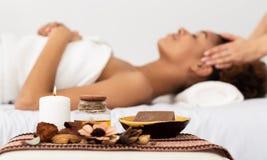 Termas do aroma Mulher do Afro que aprecia a massagem facial em termas luxuosos fotografia de stock