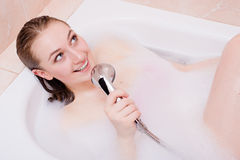Termas do canto: usando o chuveiro como a jovem mulher bonita de sorriso feliz atrativa da menina loura do microfone que relaxa t Imagens de Stock