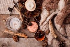 Termas e bem-estar que ajustam-se com sal do mar, essência do óleo, cones e vela, decoração de madeira no fundo de madeira imagens de stock
