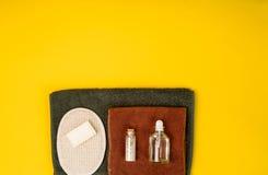 Termas ou bem-estar que ajustam-se nas cores brancas As garrafas com aroma essencial lubrificam, as toalhas, sabão no fundo amare Foto de Stock