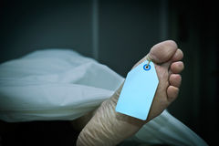 Terminal Athlete's Foot. Closeup of foot in a morgue with blank tag hanging from the big toe. Foot clearly shows flaking skin and athlete's foot fungus as well stock photography
