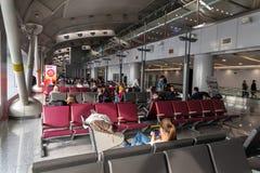 Terminal de aeroporto, com os passageiros que sentam-se ao redor fotografia de stock royalty free