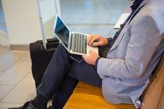 Terminal de aeropuerto de Using Laptop In del hombre de negocios Fotos de archivo libres de regalías