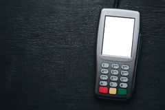 Terminal de carte de crédit sur le bureau en bois foncé Photo stock