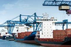Terminal de contenedores con las grúas de pórtico y los buques de carga descargados a Foto de archivo