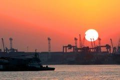 Terminal de contenedores en la puesta del sol Imagenes de archivo