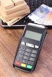 Terminal de paiement avec des devises euro, ordinateur portable et boîtes sur la palette, payant l'expédition et les produits Photos stock