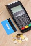 Terminal de paiement avec la carte de crédit et argent de poli sur le bureau, concept de finances Photographie stock libre de droits