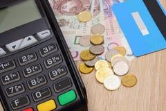 Terminal de paiement avec la carte de crédit et argent de poli sur le bureau, concept de finances Photographie stock