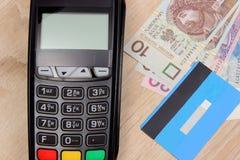 Terminal de paiement avec la carte de crédit et argent de poli sur le bureau, concept de finances Images libres de droits