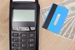 Terminal de paiement avec la carte de crédit et argent sur le bureau, concept de finances Photos stock