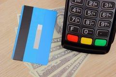 Terminal de paiement avec la carte de crédit et argent sur le bureau, concept de finances Photos libres de droits