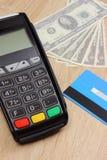 Terminal de paiement avec la carte de crédit et argent sur le bureau, concept de finances Photo libre de droits
