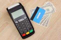 Terminal de paiement avec la carte de crédit et argent sur le bureau, concept de finances Photographie stock