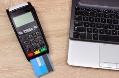 Terminal de paiement avec la carte de crédit et l'ordinateur portable, concept de finances Photographie stock libre de droits