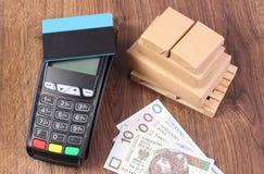 Terminal de paiement avec la carte de crédit, l'argent polonais de devise et les boîtes enveloppées sur la palette en bois Image stock