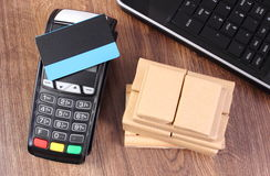 Terminal de paiement avec la carte de crédit, l'ordinateur portable et les boîtes enveloppées sur la palette en bois, payant des  Image stock