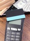 Terminal de paiement avec la carte de crédit, les devises dollar, l'ordinateur portable et les boîtes enveloppées sur la palette  Image libre de droits