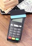 Terminal de paiement avec la carte de crédit, les devises dollar, l'ordinateur portable et les boîtes enveloppées sur la palette  Images stock