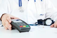Terminal de paiement dans le doctor& x27 ; bureau de s Salaire pour des soins de santé photographie stock
