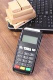 Terminal de paiement, ordinateur portable et petites boîtes enveloppées sur la palette, paiement sans argent embarquer et produit Image stock