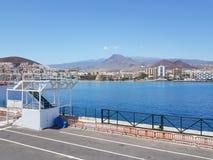Terminal de transbordadores en el ` s Tenerife de Las Cristiano con los apartamentos del día de fiesta y las montañas rocosas en  imagenes de archivo