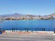 Terminal de transbordadores en el ` s Tenerife de Las Cristiano con los apartamentos del día de fiesta y las montañas rocosas en  fotografía de archivo