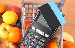 Terminal del pago con la tarjeta de crédito sin contacto, frutas y verduras, concepto de pagar cashless hacer compras fotografía de archivo