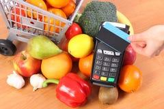 Terminal del pago con la tarjeta de crédito sin contacto y frutas y verduras, el pagar cashless concepto que hace compras foto de archivo libre de regalías