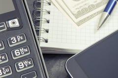 Terminal del pago, smartphone con la tecnología de NFC para pagar cashless en diversos lugares, libreta y dólar de las monedas imagen de archivo