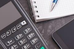 Terminal del pago, smartphone con tecnología de NFC y libreta para las notas Concepto Cashless el pagar y del negocio imagenes de archivo