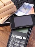 Terminal do pagamento com telefone celular com tecnologia de NFC, moedas euro, portátil e as caixas envolvidas na pálete de madei Imagens de Stock