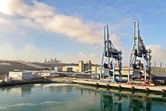 Terminal do trnsbordo para descarregar a carga de maioria do enxofre químico dos navios usando um guindaste litoral Porto de Zorf imagem de stock royalty free