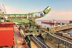 Terminal do trnsbordo para descarregar a carga de maioria do enxofre químico dos navios usando um guindaste litoral Porto de Zorf fotografia de stock