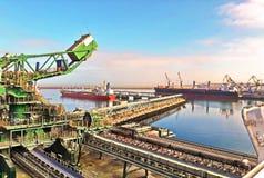 Terminal do trnsbordo para descarregar a carga de maioria do enxofre químico dos navios usando um guindaste litoral Porto de Zorf fotografia de stock royalty free