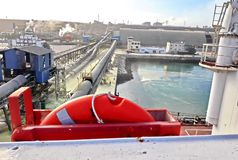 Terminal do trnsbordo para descarregar a carga de maioria do enxofre químico dos navios usando um guindaste litoral Porto de Zorf fotos de stock royalty free