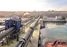 Terminal do trnsbordo para descarregar a carga de maioria do enxofre químico dos navios usando um guindaste litoral Porto de Zorf imagens de stock