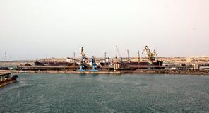 Terminal do trnsbordo para descarregar a carga de maioria do enxofre químico dos navios usando um guindaste litoral Porto de Zorf imagens de stock royalty free