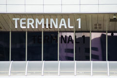 Terminal inscription at the airport with reflection in window. Terminal 1 inscription at the airport with reflection in window Stock Image