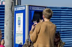 Terminal for payment of parking in the car park. People make the payment. Close-up. Russia stock photography