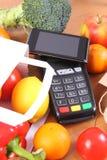 Terminal y smartphone con tecnología de NFC, frutas y verduras, el pagar cashless del pago hacer compras foto de archivo