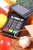 Terminal y smartphone con tecnología de NFC, frutas y verduras, el pagar cashless del pago hacer compras imagen de archivo