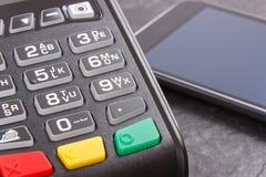 Terminal y smartphone del pago con tecnología de NFC usando para pagar cashless en diversos lugares Concepto de las finanzas imagen de archivo