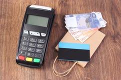 Terminale di pagamento con la carta di credito, le valute euro ed il sacchetto della spesa della carta, concetto di pagamento com Fotografia Stock
