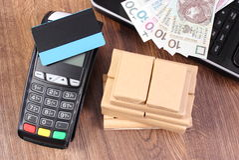 Terminale di pagamento con la carta di credito, i soldi polacchi, il computer portatile e le scatole avvolte sul pallet di legno Fotografia Stock Libera da Diritti