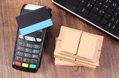 Terminale di pagamento con la carta di credito, il computer portatile e le scatole avvolte sul pallet di legno, pagante i prodott Immagine Stock