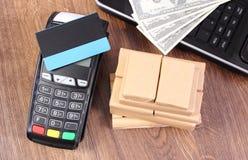 Terminale di pagamento con la carta di credito, le valute dollaro, il computer portatile e le scatole avvolte sul pallet di legno Fotografie Stock
