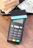 Terminale di pagamento con la carta di credito, le valute dollaro, il computer portatile e le scatole avvolte sul pallet di legno Immagini Stock